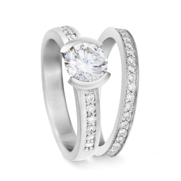 Platinum diamond partial bezel engagement ring with bead set side diamonds and matching bead set diamond wedding band by Cronin Jewelers