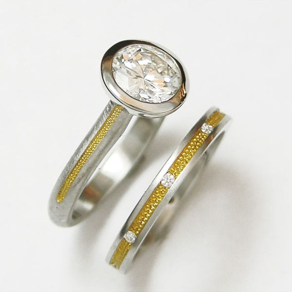 Platinum and 24kt. yellow gold bezel set Diamond engagement ring with matching     Platinum and 24kt. diamond wedding band by Cronin Jewelers